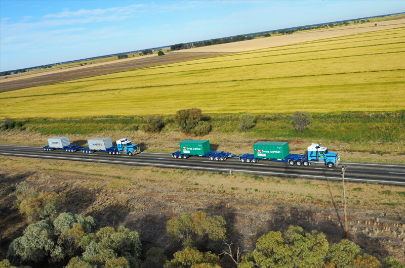 Griffith Tours New South Wales - arial photo of two road trains travelling down a highway that cuts through a Griffith wheat field.